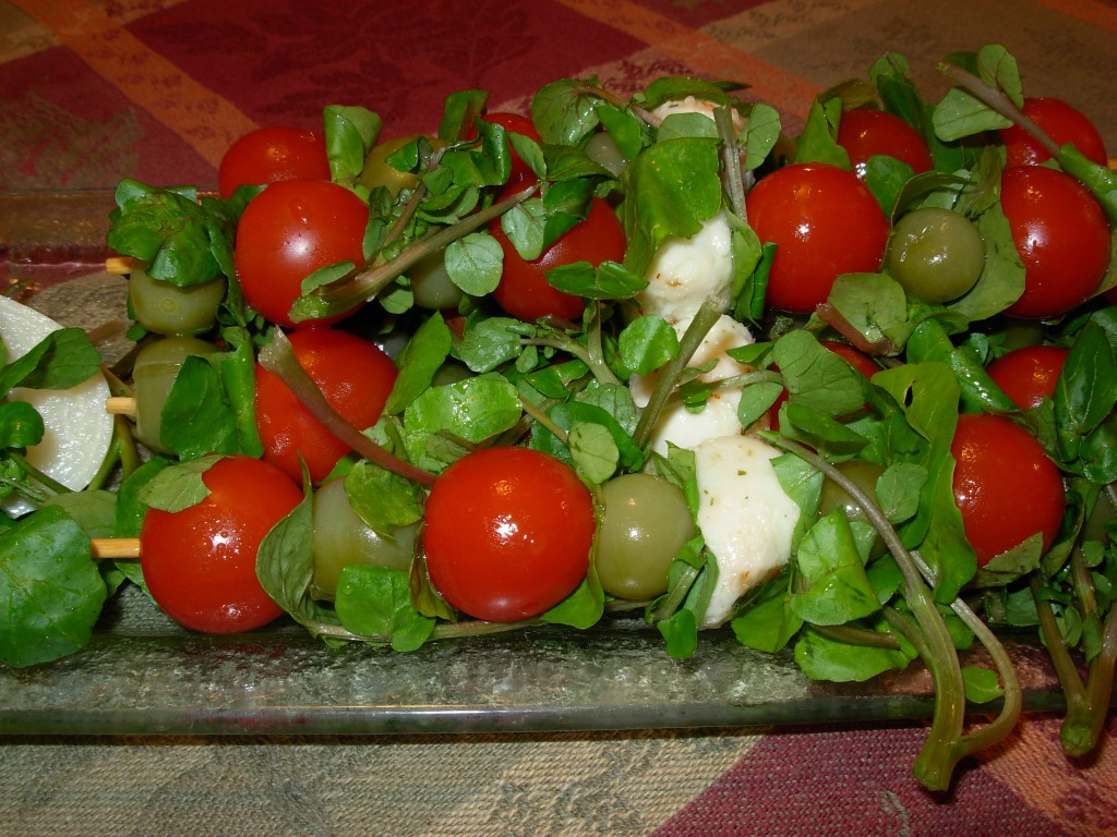 Salad kebobs made with dill pickled green cherry tomatoes, fresh red cherry tomatoes, fresh mozzarella and water cress.