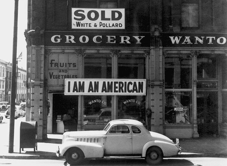 A Japanese American unfurled this banner the day after the Pearl Harbor attack. Dorothea Lange photographed it in March 1942, just prior to the man's internment. Wikimedia Commons.