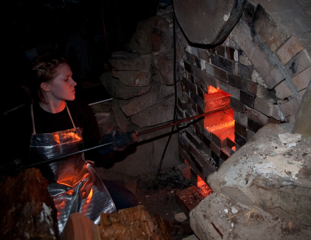Mya Hoskisson tending the furnace's front door. At 16, she's been hanging around the anagama kiln since she was in the womb. Photo: RICHARD YATES