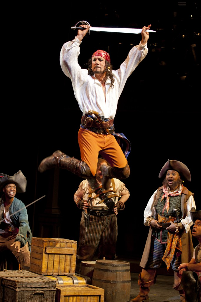 Enter the Pirate King (Michael Elich) as his shipmates look on with awe (Rodney Gardiner, Daniel T. Parker, Kimberly Scott, Christopher Livingston). Photo: T. Charles Erickson.